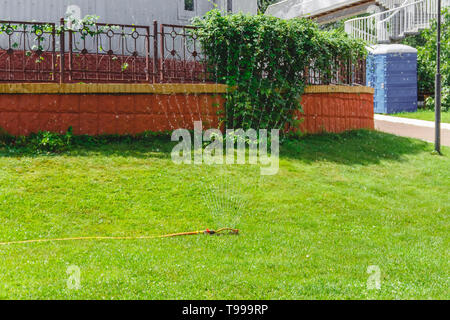 Drip fountain watering system in the garden near the house. - Stock Photo