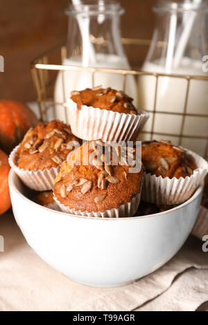 Tasty pumpkin muffins with sunflower seeds in bowl on table - Stock Photo