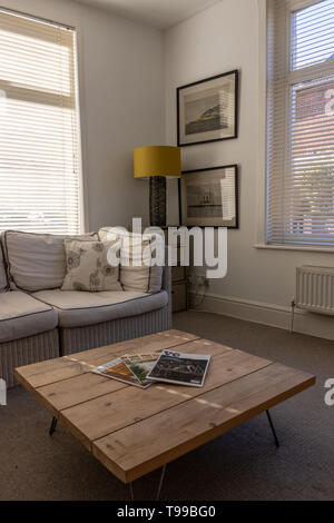 A modern light Living room in and English home with wooden coffee table and interior design magazines in the foreground