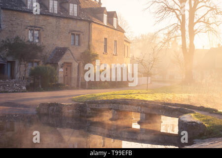 Lower Slaughter in the Cotswolds on a misty sunrise. Bridge over River Windrush leads to cottages - Stock Photo
