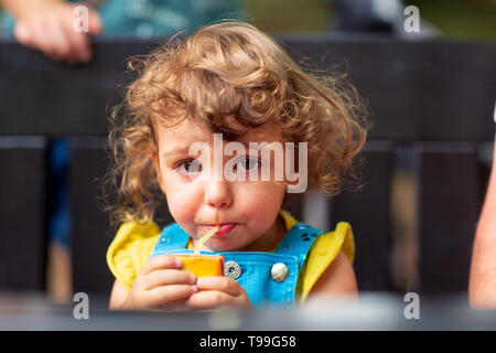 Cute kid girl drinking juice in park - Stock Photo