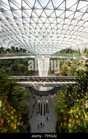 18.04.2019, Singapore, , Singapore - View into the Forest Valley with waterfall in the new Jewel Terminal at Changi International Airport. The design  - Stock Photo