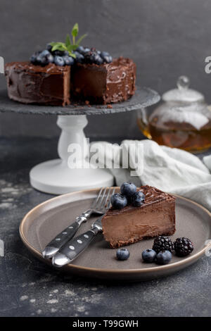Piece of chocolate cake with whole cake behind on gray background. Concept of sweet holiday food. Side view - Stock Photo