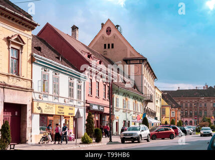 SIGHISOARA, ROMANIA - April 9, 2019: Street view of Sighisoara on a sunny day with people strolling and many cars parked.