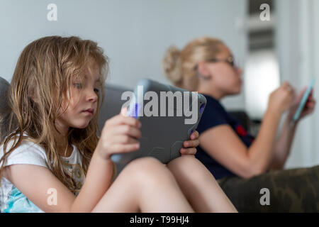 Girls are sitting on sofa and reading. Woman holds tablet while girl has phone in hands