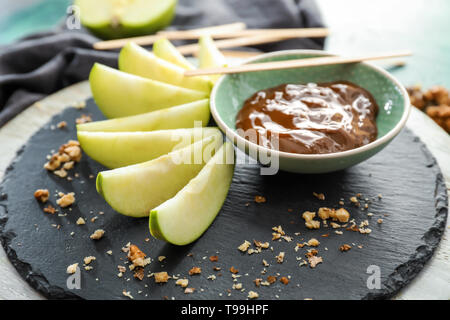Plate with sauce and apple slices on slate plate - Stock Photo