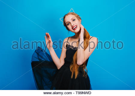 Young pretty woman with beautiful smile, fluttering black dress, posing on blue background. She has long hair, wearing headband with cat ears, nice make up with red lipstick. - Stock Photo