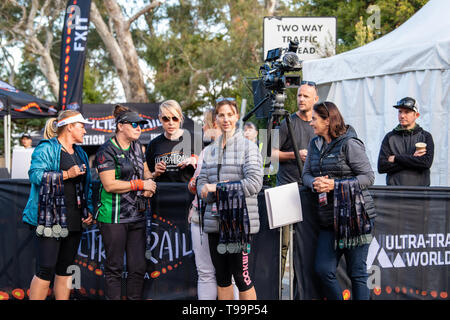 Blue Mountains, Australia - April 16 2019: Ultra-Trail Australia UTA11 race. Volunteers handing out medals at the finish line. - Stock Photo