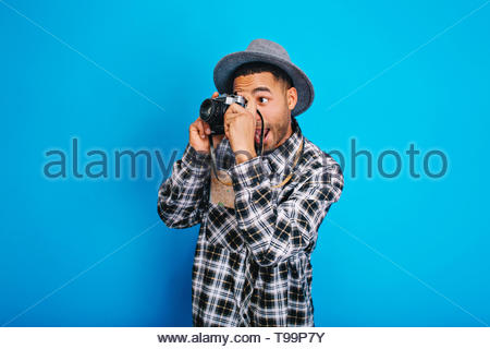 Portrait funny excited tourist guy in hat making photo on camera on blue background. Having fun, enjoying holidays, weekends, travelling around the world, expressing positivity - Stock Photo
