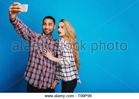 Stylish handsome guy making selfie portrait with attractive young woman with long blonde hair on blue background. Having fun, cheerful mood, relaxing, free time, hobby. Place for text - Stock Photo