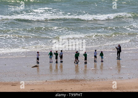 Southsea, Portsmouth, England, UK. May 2019.  A line of school children playing on the  beach with a backdrop of waves at Southsea an English resort. - Stock Photo