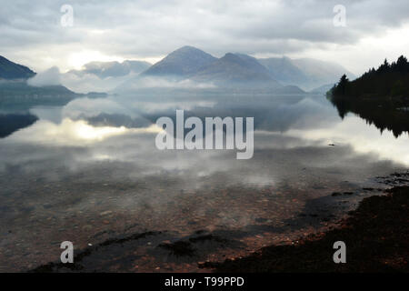 A photograph across Loch Duich towards The Five Sisters of Kintail on a misty spring morning - Stock Photo
