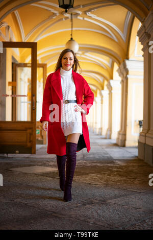 feshion woman in a red jacket standing on the street - Stock Photo