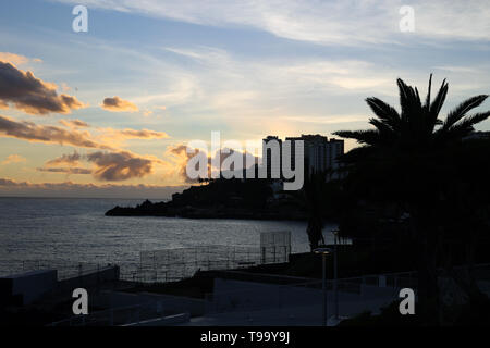 Colorful landscape with a stunning sunset located in Funchal, Madeira. The sky is colored with orange, gold and blue. Beautiful! - Stock Photo
