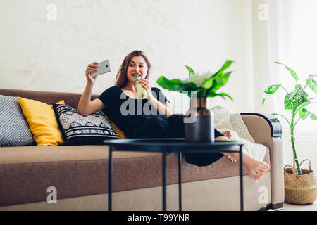 Happy young woman relaxing in living room and drinking smoothie. Healthy diet - Stock Photo
