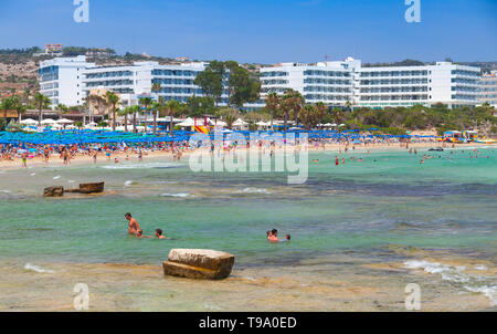 Ayia Napa, Cyprus - June 12, 2018: People rest in sea water. Public beach of Ayia Napa resort town at the far eastern end of the southern coast of Cyp - Stock Photo