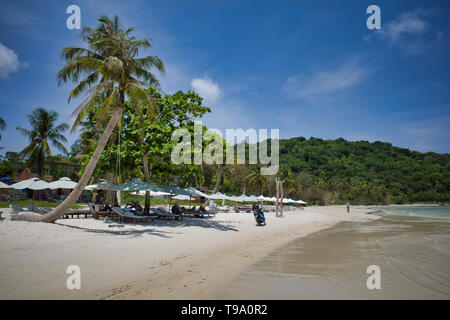 Phu Quoc island, Vietnam - March 27, 2019: Tourists walking on beautiful Sao beach with white sand and palm trees - Stock Photo