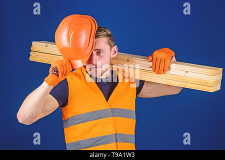 Protective equipment concept. Carpenter, woodworker, labourer, builder carries wooden beam on shoulder. Man in protective gloves holds visor of helmet, corrects hard hat on head, blue background. - Stock Photo