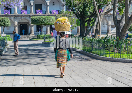 Woman in traditional Guatemalan clothing, walking through central park with a basket on her head and a historic building, in Antigua, Guatemala - Stock Photo