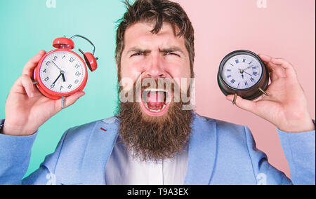Changing time zones affect health. Does changing clock mess with your health. Man bearded hipster hold two different clocks. Guy unshaven puzzled face having problems with changing time. Time zone. - Stock Photo