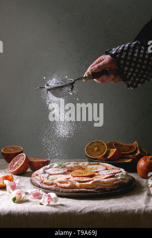 Young man's hand sprinkling sugar powder homemade Cheesecake with sicilian blood oranges, decorated by edible flowers, mint leaves served on grey line - Stock Photo