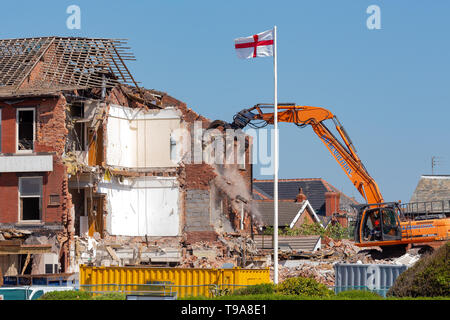 demolition work in progress as the chadwick hotel on the promenade of st annes on sea is broken down under the watch of the flag of st george - Stock Photo