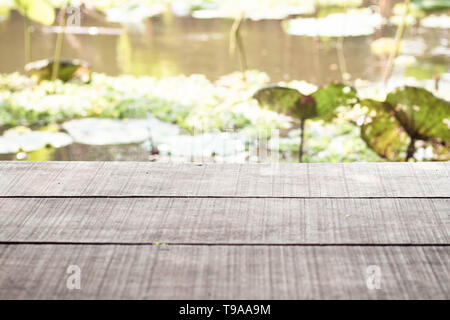 old wooden table and the lake with Asian tropical lake lotus  in background.nature.holiday.Asia - Stock Photo