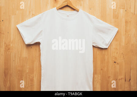 white short sleeve t-shirt plain round neck mock up concept idea wooden back ground  front view - Stock Photo