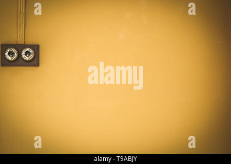 Antique light switch on yellow color wall inst background in the vintage house - Stock Photo