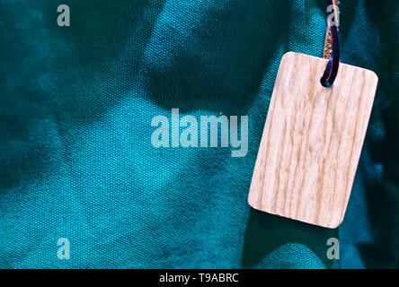 wooden tag with thin leather cord blue green canvas close up texture background - Stock Photo