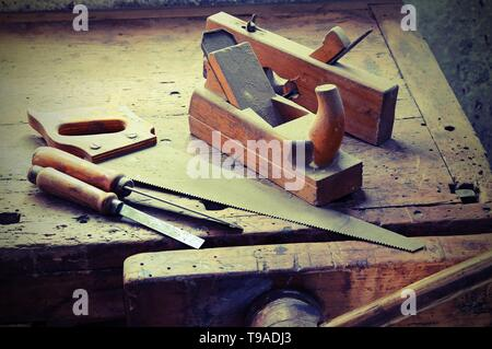 planes and chisels and a saw on the Workbench with a vise  with old toned effect - Stock Photo