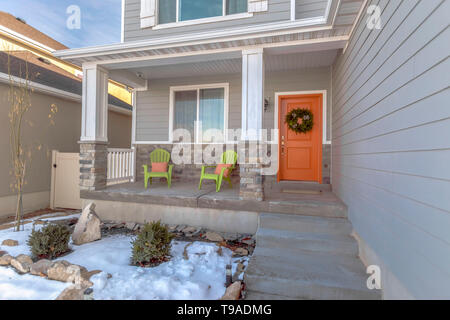 Facade of a home with stairs leading to the porch and front door with wreath - Stock Photo