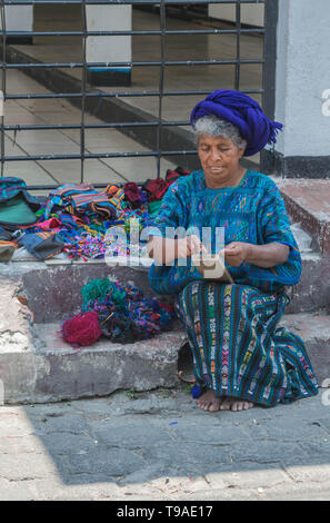 Guatemalan woman in traditional clothing and a blue head scarf sitting on a stone step weaving crafts to sell on the street, in Panajachel, Guatemala - Stock Photo