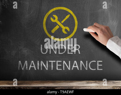 text UNDER MAINTENANCE and icon on chalkboard with hand holding piece of chalk - Stock Photo