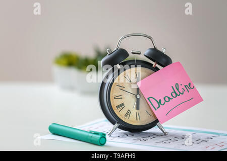 Paper with word DEADLINE and alarm clock on calendar - Stock Photo