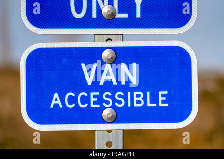 Blue sign with a Van Accessible text on a parking area for handicapped people - Stock Photo