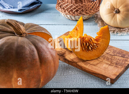 Bright orange pumpkin and its two slices with seeds on cutting board and on blue wooden surface. Pumpkin, cloth and basket at background. Selective fo - Stock Photo