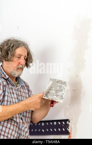 Builder repairing a crack in a wall mixing plaster on a handheld plate with a spatula ready to apply the furnishing touches to the surface, focus to t - Stock Photo