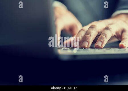 Low angle view from the back of the computer of a businessman typing on a laptop computer keyboard in a retro vintage toned image. - Stock Photo