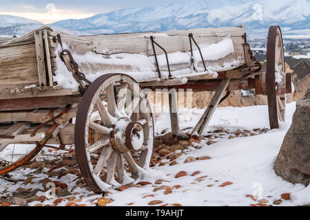 A worn out wooden wagon with rusty wheels and powdery snow viewed in winter - Stock Photo
