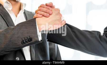 Close up of two businessmen in gray business suit gripping their hands in success and agreement at the office. - Stock Photo