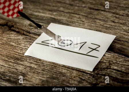 Dart stuck on 2017 date handwritten on rectangular white sheet of paper over wooden table. - Stock Photo