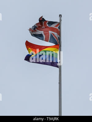 Westminster, London, UK, 17th May 2019. On International Day Against Homophobia, Biphobia and Transphobia, which is every year on 17th May, a rainbow coloured flag flies alongside the Union Jack on top 100 Parliament Street in Westminster. The building houses Her Majesty's Revenue and Customs. Credit: Imageplotter/Alamy Live News - Stock Photo