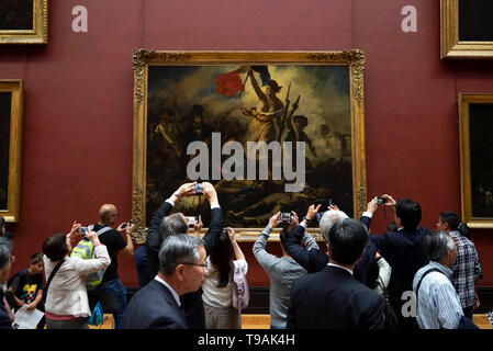 Beijing, France. 15th May, 2019. People take pictures of La Liberte guidant le peuple, or Liberty Leading the People, by Eugene Delacroix displayed at the Louvre Museum in Paris, France, May 15, 2019. Saturday marks the International Museum Day. Credit: Alexandre Karmen/Xinhua/Alamy Live News - Stock Photo