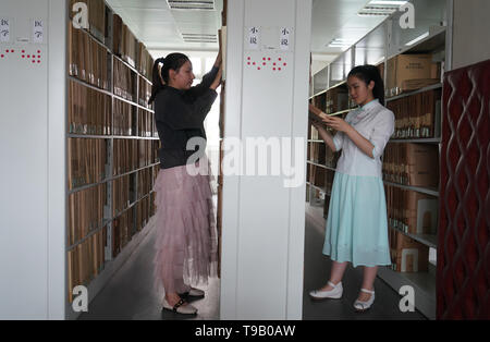 (190518) -- NANJING, May 18, 2019 (Xinhua) -- Wu Yifan(L) and Zhou Wenqing pick up books in a braille library of Nanjing Normal University of Special Education in Nanjing, east China's Jiangsu Province, May 17, 2019. Wu Yifan, 22, and Zhou Wenqing, 21, are schoolmates in Nanjing Normal University of Special Education. Both of them lost eyesight in their childhood.   In their spare time, Wu likes doing makeup, paper-cutting as well as playing the Guzheng, Chinese Zither. While Zhou enjoys playing the piano. Zhou once developed a computer game for visually impaired people.   The two girls have p - Stock Photo