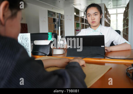 (190518) -- NANJING, May 18, 2019 (Xinhua) -- Wu Yifan(L) and Zhou Wenqing study in a braille library of Nanjing Normal University of Special Education in Nanjing, east China's Jiangsu Province, May 17, 2019. Wu Yifan, 22, and Zhou Wenqing, 21, are schoolmates in Nanjing Normal University of Special Education. Both of them lost eyesight in their childhood.   In their spare time, Wu likes doing makeup, paper-cutting as well as playing the Guzheng, Chinese Zither. While Zhou enjoys playing the piano. Zhou once developed a computer game for visually impaired people.   The two girls have passed th - Stock Photo