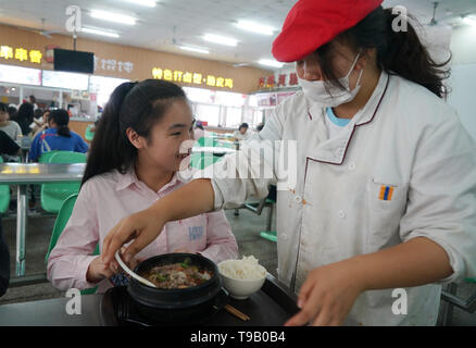 (190518) -- NANJING, May 18, 2019 (Xinhua) -- A staff member sends meals to Zhou Wenqing (L) in a canteen of Nanjing Normal University of Special Education in Nanjing, east China's Jiangsu Province, May 17, 2019. Wu Yifan, 22, and Zhou Wenqing, 21, are schoolmates in Nanjing Normal University of Special Education. Both of them lost eyesight in their childhood.   In their spare time, Wu likes doing makeup, paper-cutting as well as playing the Guzheng, Chinese Zither. While Zhou enjoys playing the piano. Zhou once developed a computer game for visually impaired people.   The two girls have passe - Stock Photo