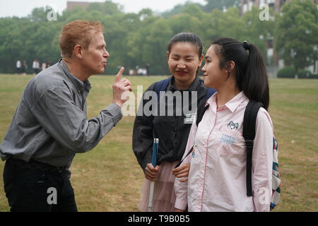 (190518) -- NANJING, May 18, 2019 (Xinhua) -- Wu Yifan (C) and Zhou Wenqing (1st R) communicate with their foreign teacher in Nanjing Normal University of Special Education in Nanjing, east China's Jiangsu Province, May 17, 2019. Wu Yifan, 22, and Zhou Wenqing, 21, are schoolmates in Nanjing Normal University of Special Education. Both of them lost eyesight in their childhood.   In their spare time, Wu likes doing makeup, paper-cutting as well as playing the Guzheng, Chinese Zither. While Zhou enjoys playing the piano. Zhou once developed a computer game for visually impaired people.   The two - Stock Photo