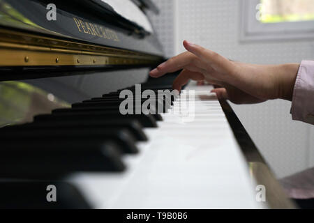 (190518) -- NANJING, May 18, 2019 (Xinhua) -- Zhou Wenqing plays the music composed by herself at the piano room in Nanjing Normal University of Special Education in Nanjing, east China's Jiangsu Province, May 17, 2019. Wu Yifan, 22, and Zhou Wenqing, 21, are schoolmates in Nanjing Normal University of Special Education. Both of them lost eyesight in their childhood.   In their spare time, Wu likes doing makeup, paper-cutting as well as playing the Guzheng, Chinese Zither. While Zhou enjoys playing the piano. Zhou once developed a computer game for visually impaired people.   The two girls hav - Stock Photo