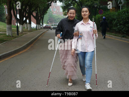 (190518) -- NANJING, May 18, 2019 (Xinhua) -- Wu Yifan(L) and Zhou Wenqing walk along the campus of Nanjing Normal University of Special Education in Nanjing, east China's Jiangsu Province, May 17, 2019. Wu Yifan, 22, and Zhou Wenqing, 21, are schoolmates in Nanjing Normal University of Special Education. Both of them lost eyesight in their childhood.   In their spare time, Wu likes doing makeup, paper-cutting as well as playing the Guzheng, Chinese Zither. While Zhou enjoys playing the piano. Zhou once developed a computer game for visually impaired people.   The two girls have passed the Col - Stock Photo